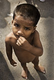 Destitute child on Indian road. A boy is having without cloths standing for food on an urban way Stock Photos