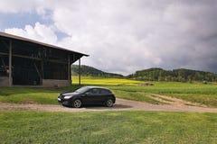 Destna, República Checa - 26 de abril de 2018: soporte negro de Opel Astra H del coche en el camino del campo que lleva al cortij Fotos de archivo libres de regalías