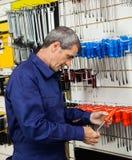 Destornillador de examen del vendedor en tienda Foto de archivo