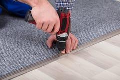 Destornillador de la radio de Installing Carpet With del ajustador de la alfombra fotos de archivo libres de regalías