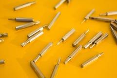 Destornillador fijado en un fondo amarillo, concepto imagen de archivo