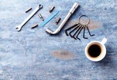 Destornillador, llaves de maleficio, llave de zócalo, pedazos para un destornillador y una taza de café en fondo de madera rústic imágenes de archivo libres de regalías