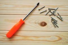 Destornillador Phillips y algunos tornillos en los tablones de madera de la madera del pino Imagen de archivo libre de regalías