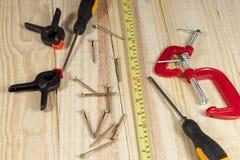 Destornillador, tornillos y una cinta métrica que pone en un piso de madera Foto de archivo libre de regalías
