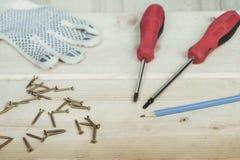 Destornillador y sistema de tornillos en fondo de madera Imágenes de archivo libres de regalías
