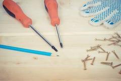 Destornillador y sistema de tornillos en fondo de madera Fotografía de archivo libre de regalías