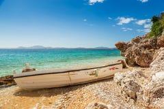 Destoyed fishing boat at rocks under bright sunlight Stock Photo