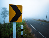 Destra di giro del segnale stradale alla foschia Immagine Stock