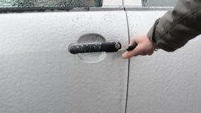 Destravando a porta de carro coberta no gelo após o blizzard vídeos de arquivo