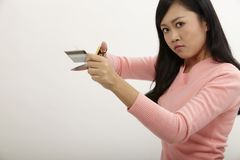 Destroy credit card. Asian holding a pair of scissors cutting credit card royalty free stock image
