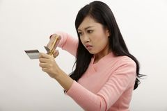 Destroy credit card. Asian holding a pair of scissors cutting credit card royalty free stock images