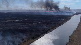 Destroy natural, large Wildfires fast moving by dry meadow with smoke going up to sky near river, aerial view