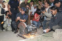 Destroy used evidence. Police officer destroying evidence used in criminal action in front of journalist in solo, central java, indonesia royalty free stock photo