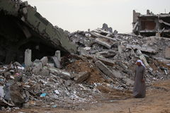 Destroyed Al Wafa Hospital, Gaza being observed by Arab man in local attire Stock Photo