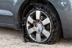 Blown out tire with exploded, shredded and damaged rubber. Destroyed blown out tire with exploded, shredded and damaged rubber on a modern suv automobile. Flat Royalty Free Stock Photo