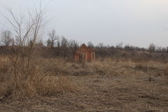 Destroyed building on the background of nature. Destroyed brick building on the background of dry grass stock image