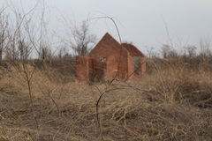 Destroyed building on the background of nature. Destroyed brick building on the background of dry grass stock images