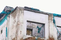 Destroyed building, housing in disrepair, demolition of the old house on grey sky background. stock image