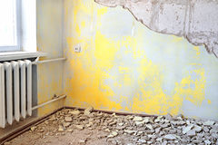 Destroyed dirty empty yellow interior with vintage radiator. Repair of apartments with old rusty cast iron central heating radiator or battery and old grungy Stock Photography