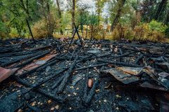Destroyed by fire wooden house completely burned to the ground.  stock photos