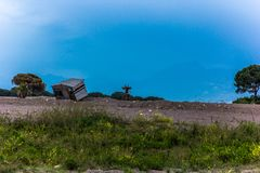 Destroyed fisherman`s house in the background, against the blue sky stock photography