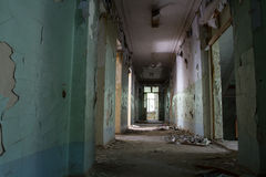 Destroyed hospital corridor. Hospital long been abandoned. With the walls crumbling plaster, doors and windows smashed. The situation is grim . Who would dare to Royalty Free Stock Photography