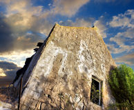 Destroyed house under dramatic sunset skies Stock Photo