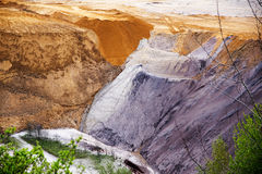 Destroyed layers of soil in the pit from lignite (brown coal) op. Encast mining, landslips of slag and sand threatens the last vegetation, a significant Royalty Free Stock Images