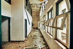 Destroyed and lowered interior of the building with broken windows with debris and glass shards on the floor. Interior walls of a destroyed building with window royalty free stock photo