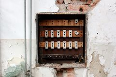 Destroyed old fuse box surrounded with crumbling wall. Destroyed rusted old fuse box surrounded with crumbling wall, visible bricks, radiator pipes and broken stock photo