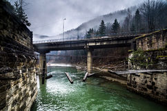 Destroyed pedestrian bridge and road-brigde over the river in mountains Royalty Free Stock Photo