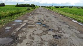 Destroyed road that needs repairs, countryside, Ukraine. Demonstration of the topic of money laundering on road repair stock video footage