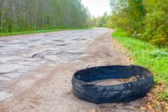 Destroyed rubber car tire car on rural bumpy broken road. Destroyed rubber car tire car on rural bumpy broken road Royalty Free Stock Photography