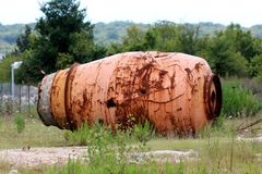 Destroyed rusted with multiple holes cement mixer truck drum taken off truck and discarded in nature surrounded with high uncut. Grass and forest in background stock images