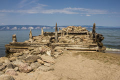Destroyed sea pier. The ruined old pier goes into the distance. In the foreground are stones, logs, sand. Nobody here. On the opposite shore white mountains Royalty Free Stock Image