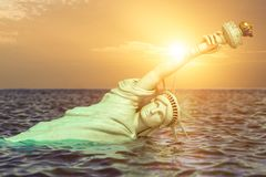Destroyed Statue of liberty in the sunset half covered by rising ocean level. Apocalypse of USA, America and the end of stock illustration