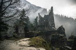 A destroyed stone structure in the foggy woods with a bridge stock images