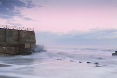Destroyed wall disappearing into the sea. Stock Photo
