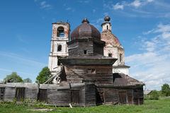 Destroyed wooden church in the background of a brick church. Royalty Free Stock Image