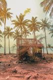 Destroyed wooden house on coastline with palm trees and beach ba stock images