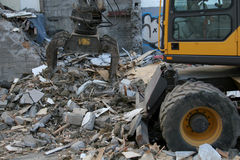 Destroying. Heavy machinery tearing down a condemned building Stock Images