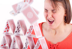 Destroying house of cards. Attractive young woman sneezes and destroys a house of cards - concept for failure or bad luck stock photography