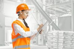 Destroying gender stereotypes. Female builder standing against industrial background. Destroying gender stereotypes. Female builder in orange helmet standing stock photography