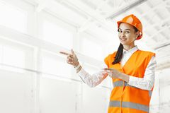 Destroying gender stereotypes. Female builder standing against industrial background. Destroying gender stereotypes. Female builder in male profession. Woman royalty free stock image