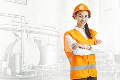 Destroying gender stereotypes. Female builder standing against industrial background. Destroying gender stereotypes. Female builder in orange helmet standing royalty free stock photo