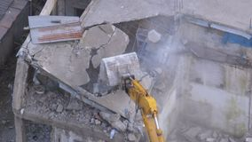 Destroying Old Concrete House Using Mechanical Arm of Bulldozer on Construction Site