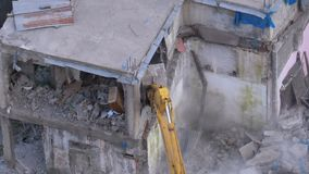 Destroying old house using bucket excavator on construction site. Slow motion.