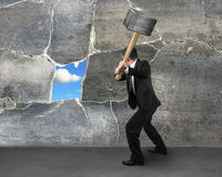 Destructing the wall with a large hammer Stock Photography