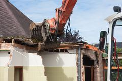 Destruction of a building by a caterpillar crane Royalty Free Stock Image