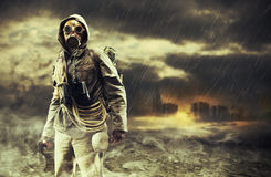 Destruction. A lonely hero wearing gas mask, city destroyed on the background